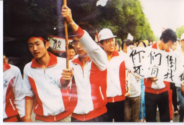 "On May 17, 1989, over 1,000 students from the High School Affiliated to Renmin University marched in support of the university students on hunger strike. The banner says: ""When you fall, you still have us!"" Jiang Jielian, on left, is one of the march's organizers"